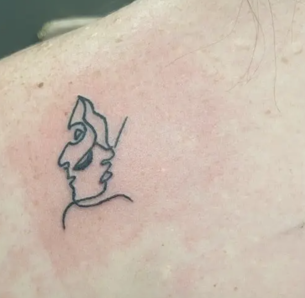 A tiny outlined tattoo of a face on someone's shoulder