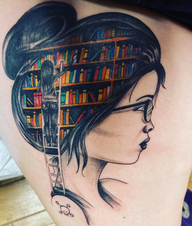 A back tattoo of a woman's head and a colorful bookshelf over her hair