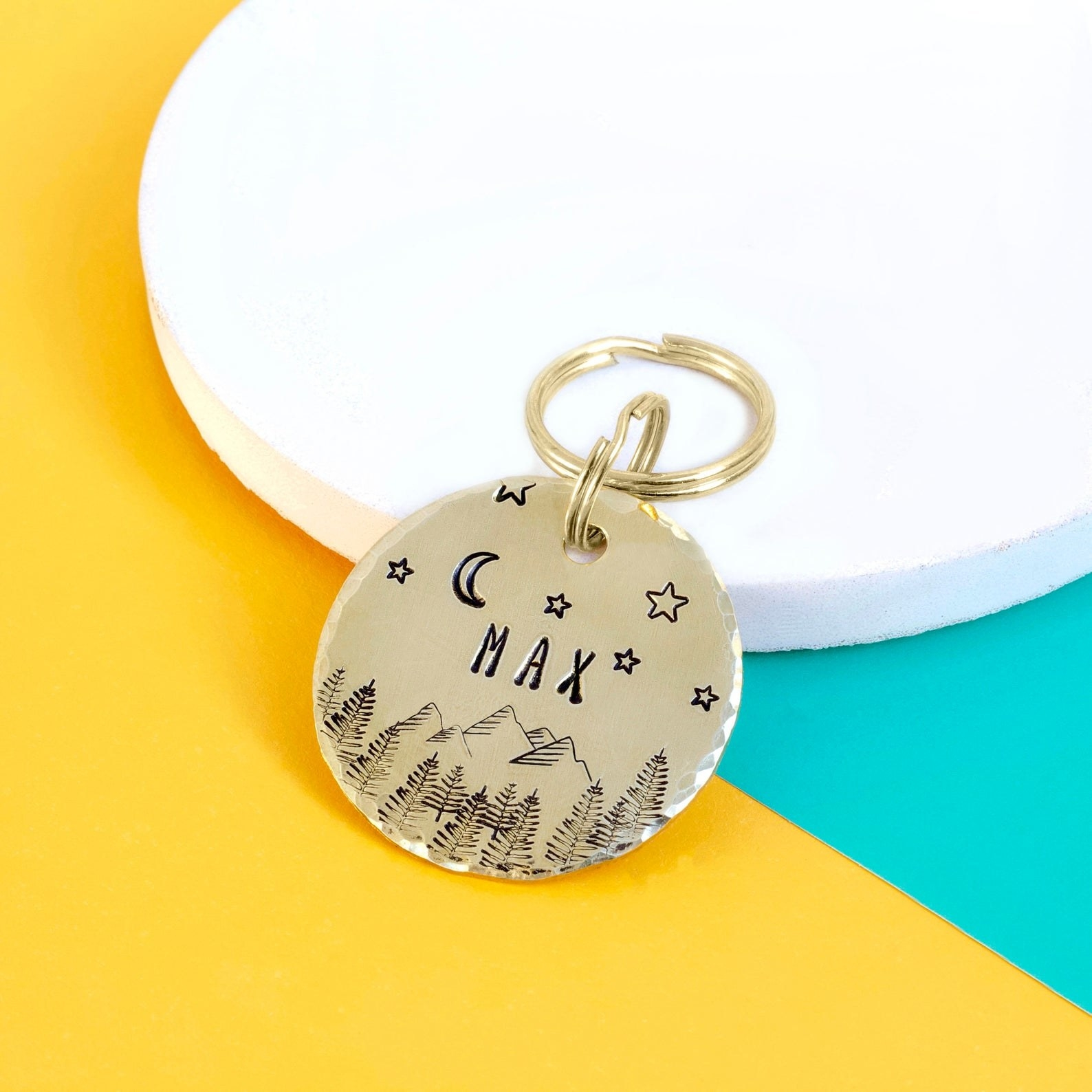 a gold dog tag with stars and mountains and trees on it