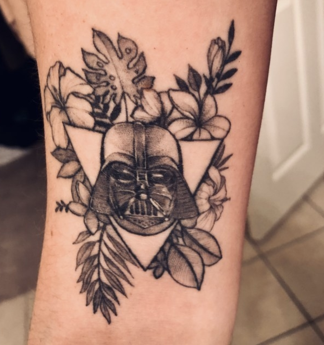 An arm tattoo with Darth Vader's helmet surrounded by flowers