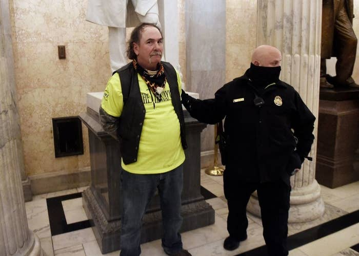 A man stands in the Capitol in front of a statue with his hands behind his back as a police officer stands next to him
