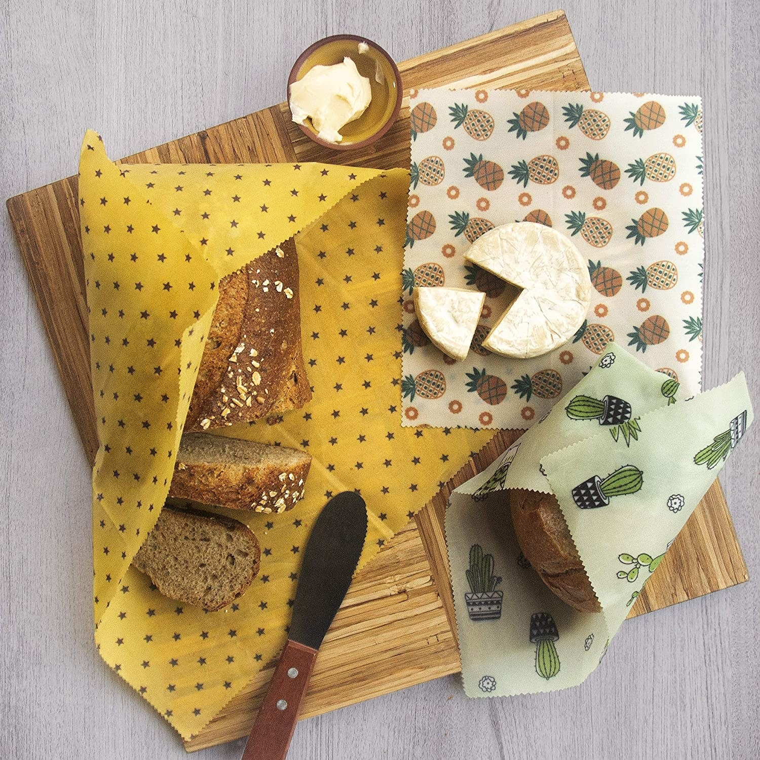 The reusable wax wraps covering cheese and bread on a cutting board