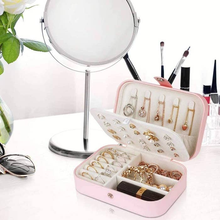 jewelry box filled with necklaces, rings, a lipstick, earrings, and bracelets