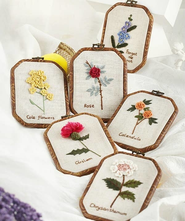 various embroidered flowers including a rose, cole flowers, calendula, forget me not, and more