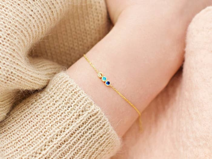 person wearing bracelet with three stones on it