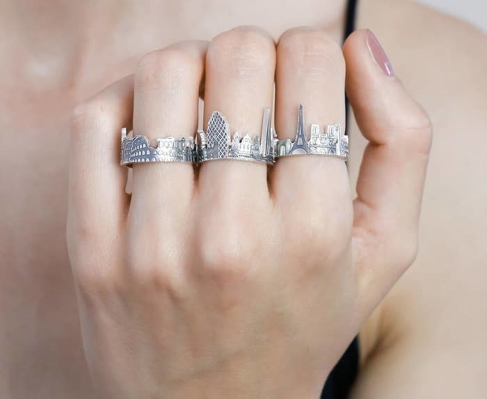 person wearing three cityscape rings
