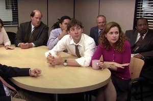 "The cast of ""The Office"" sitting at a conference table"