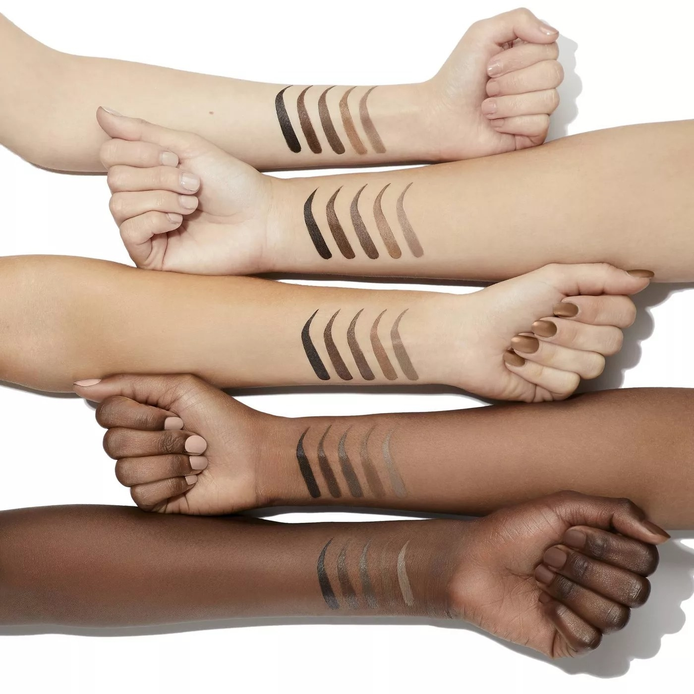 Eyebrows drawn onto the arms of models in the different shades of the sculpting pencil
