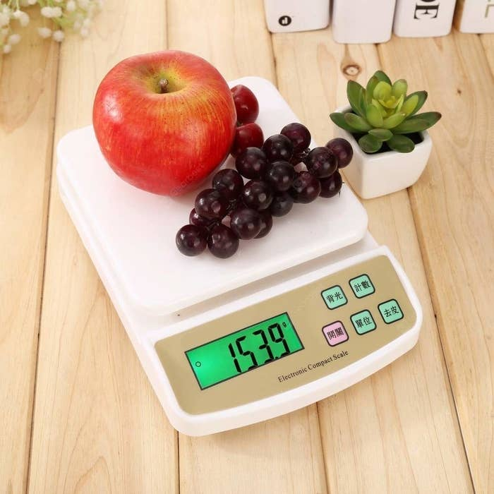A kitchen scale pictured with fruits.
