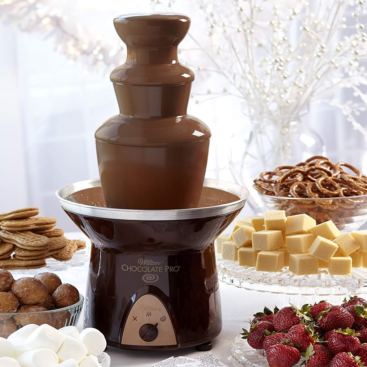The chocolate fountain in use, standing among treats for dipping
