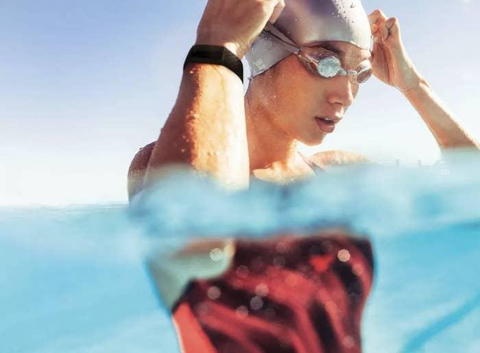 Swimmer is in water wearing a Fitbit