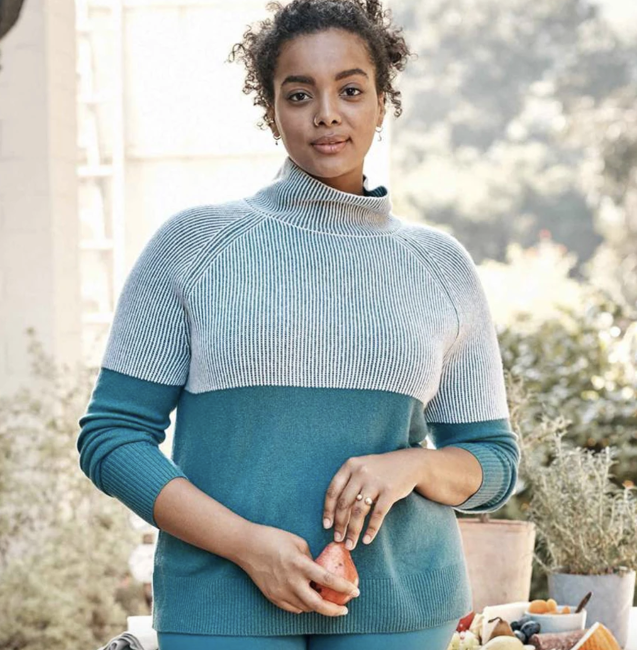 model wearing the blue sweater and striped top
