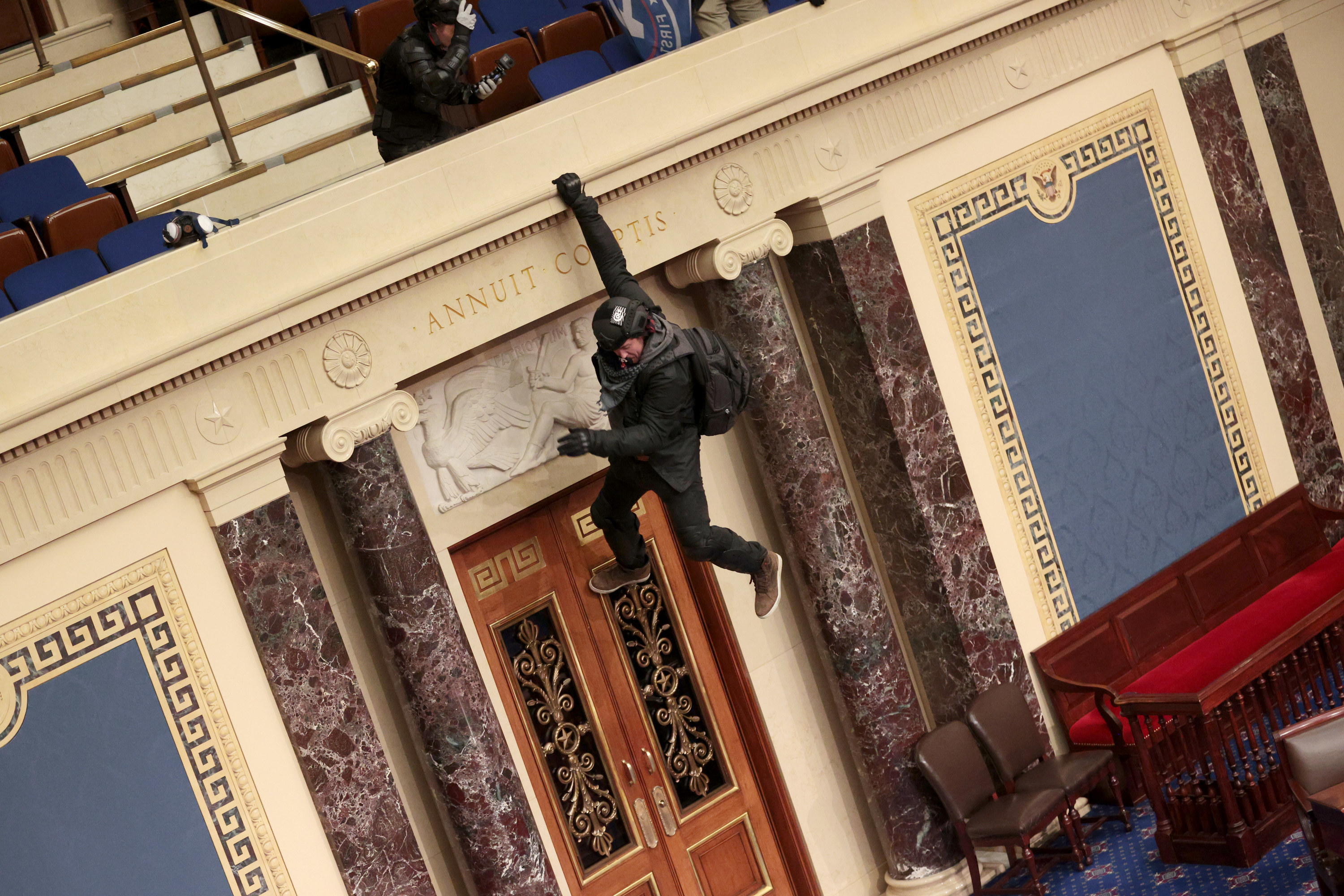 A Trump supporter hanging from the balcony of the Senate Chamber