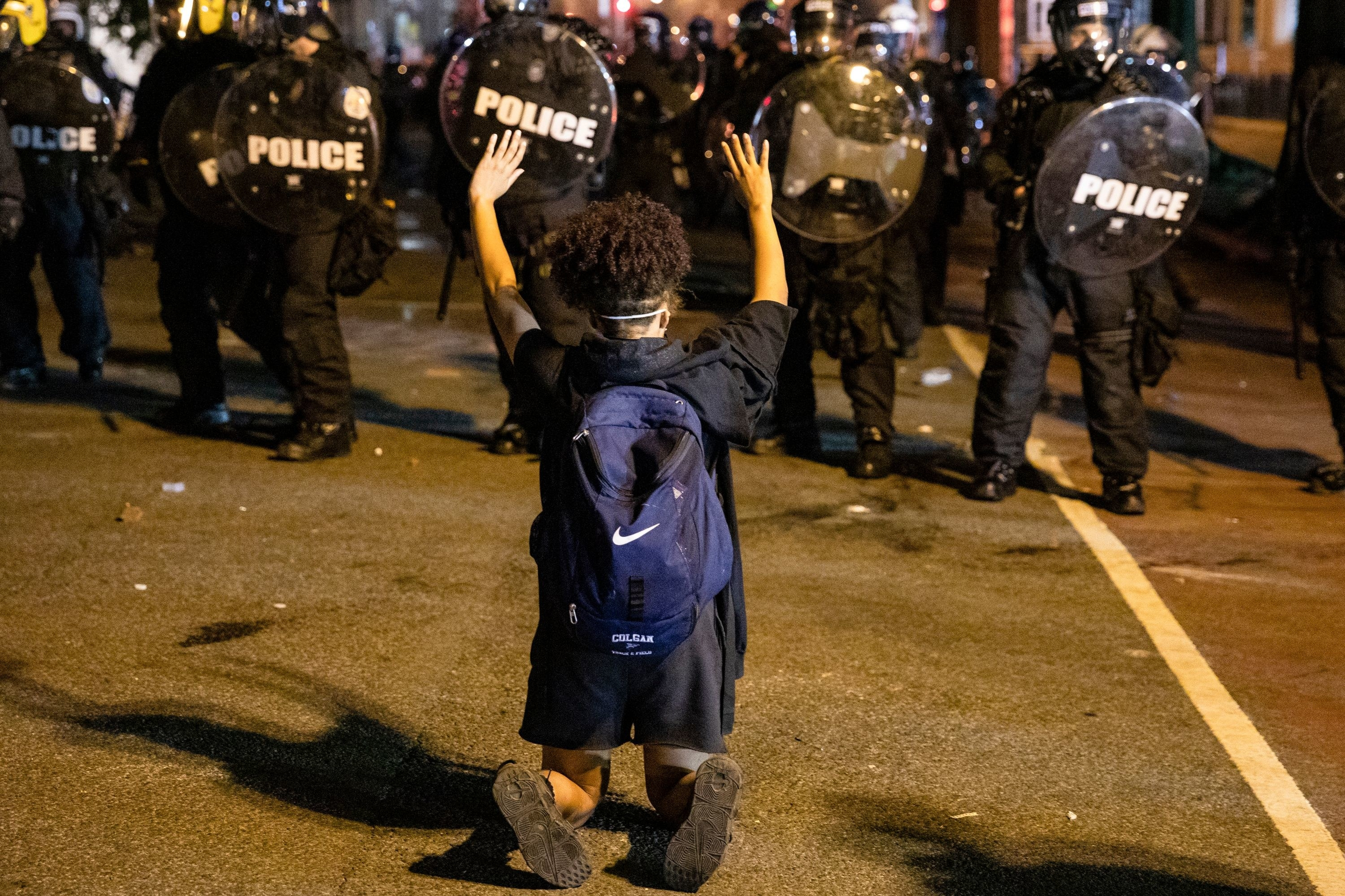 A protestor kneeing with her hands up in front of a line of police