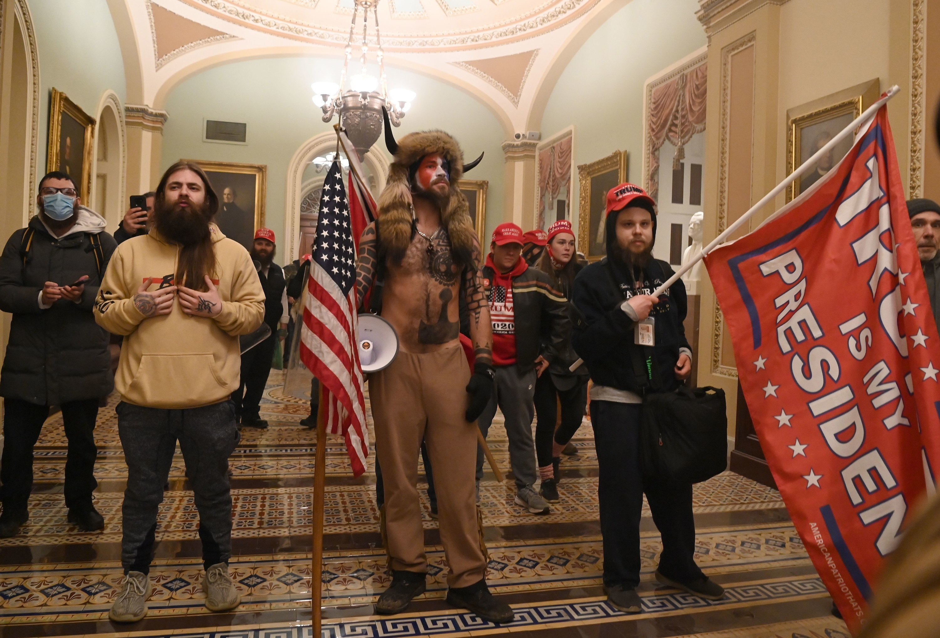 Trump supporters, include one QAnon member, stand inside the Capitol