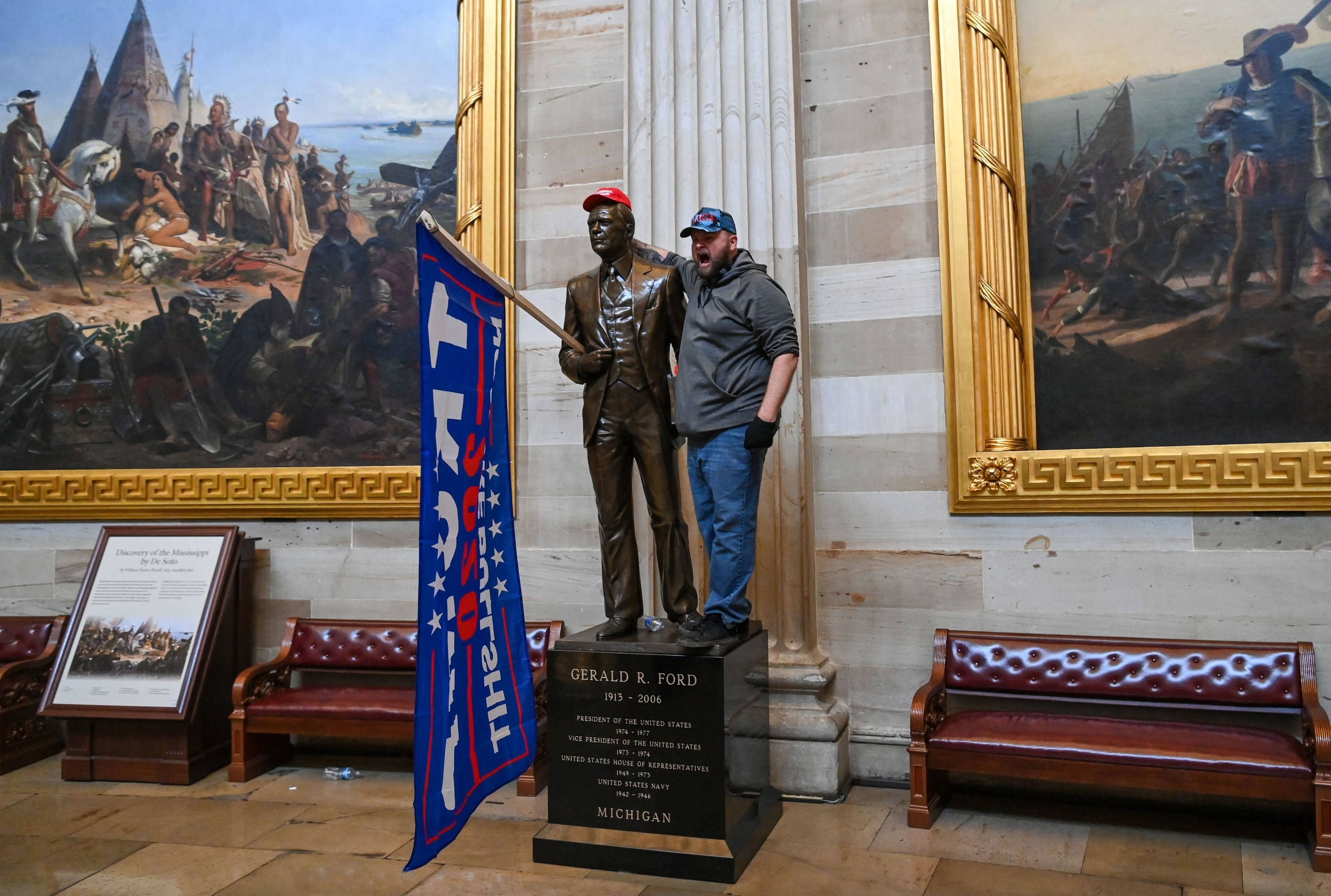 "Inside the Capitol, a Trump supporter stands next to a Gerald Ford statue that has been given a ""Make America Great Again"" hat and a Trump flag"