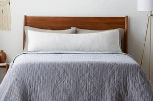 an off-white body pillow resting on a bed
