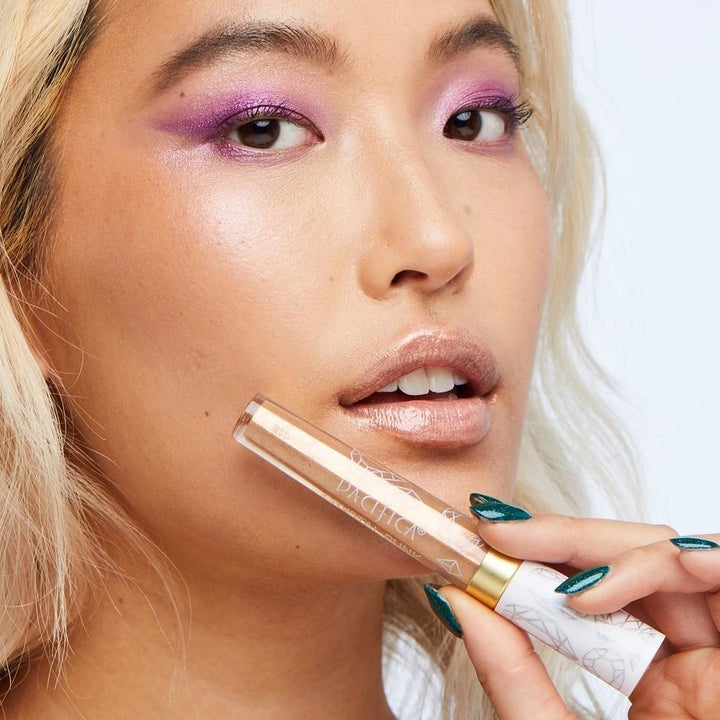 a model wearing the lip gloss and holding the tube of it