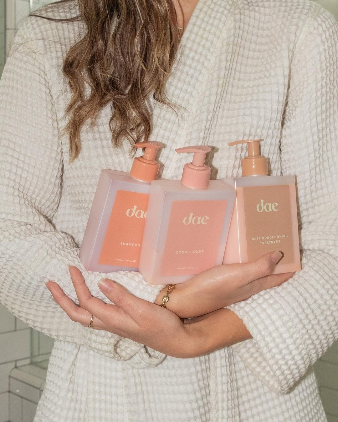 Person holding Dae hair care products