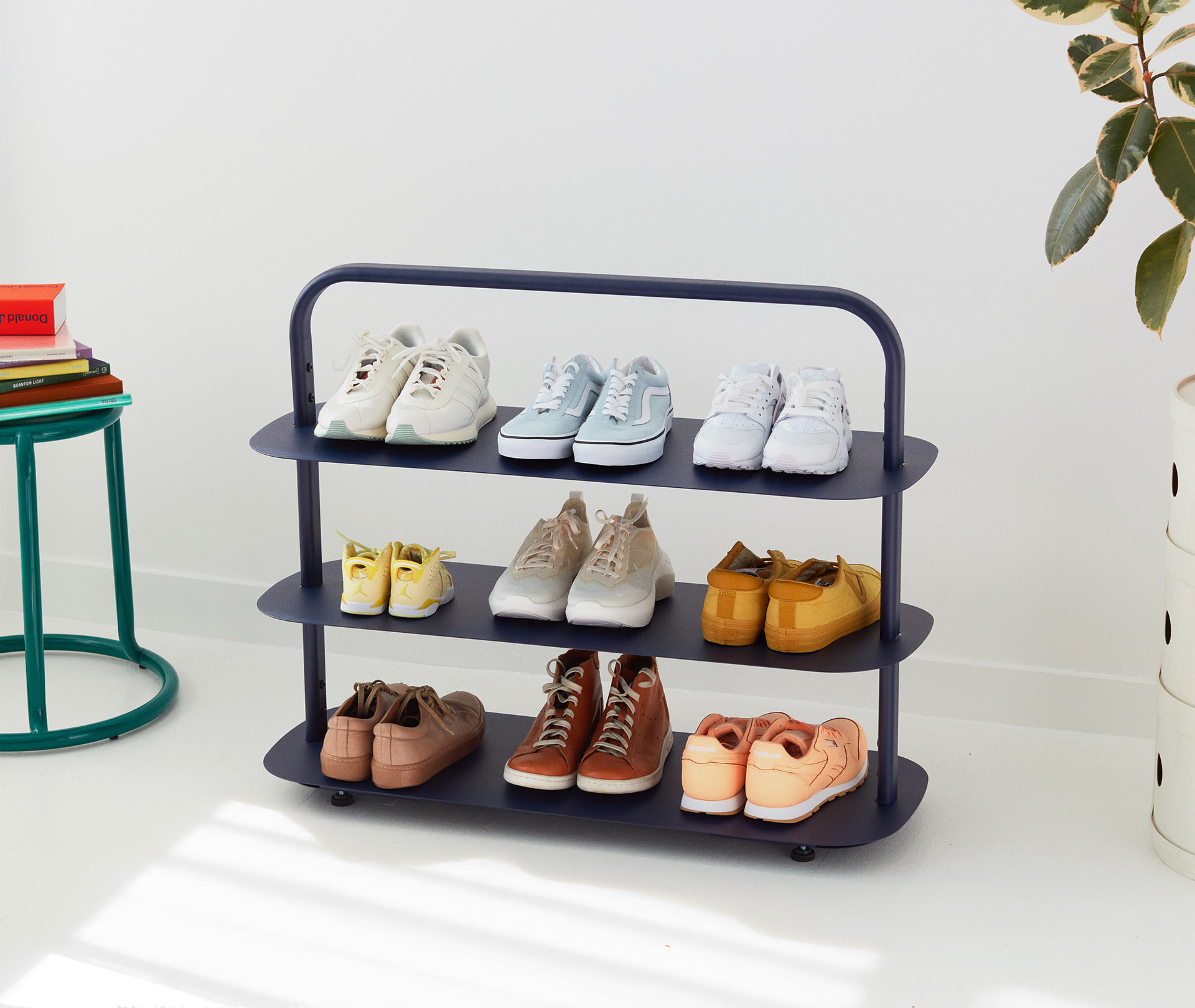 nine pairs of shoes sit on the navy entryway rack