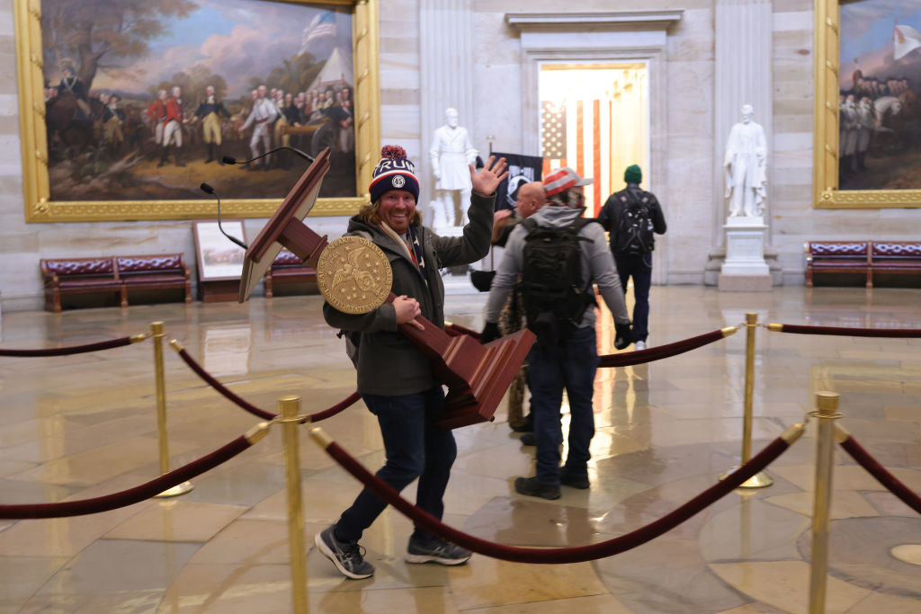 A man stealing a podium inside the Capitol