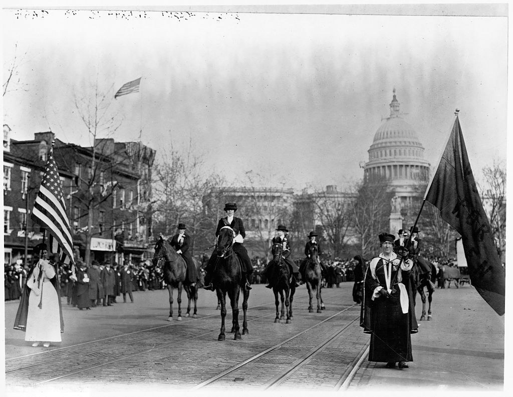 Women marching and riding horses outside the Capitol