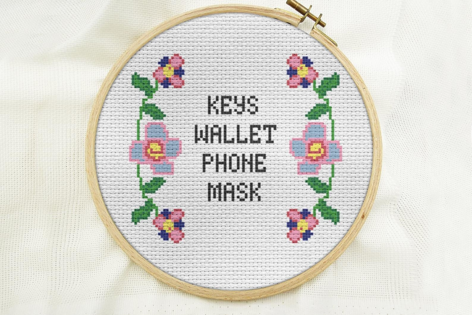 a cross stitch that says keys wallet phone mask surrounded by florals