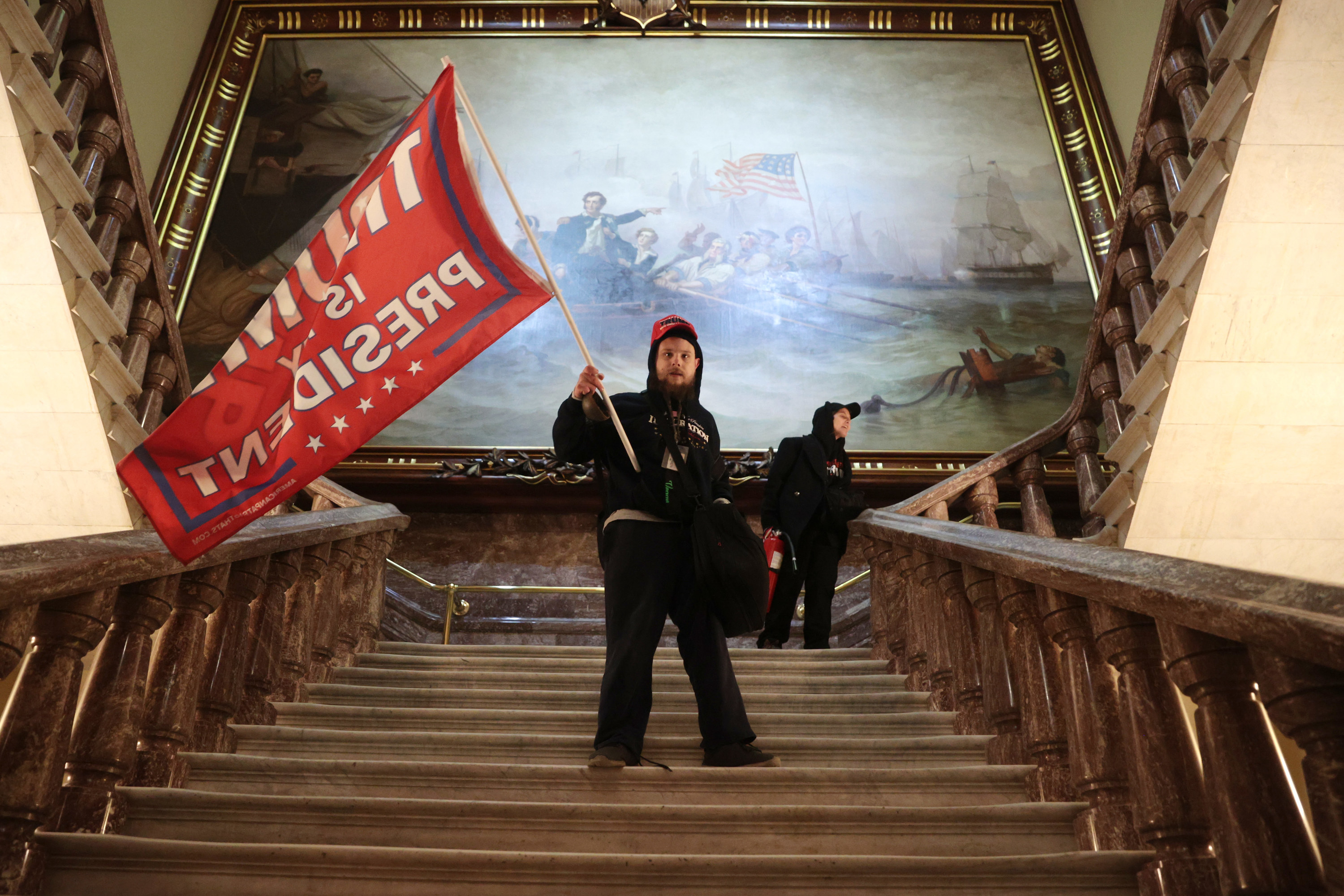 A Trump supporter waving a Trump flag in the Capitol