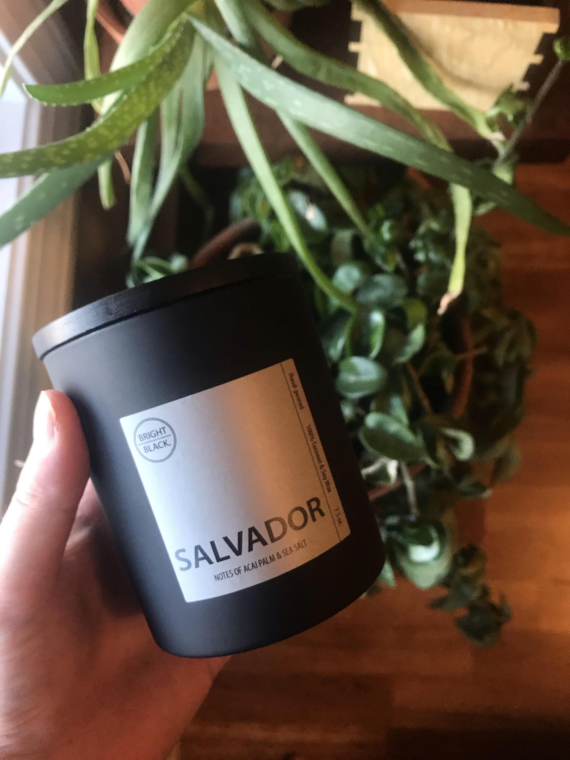 """hand holding a candle in a solid black jar with a label on it that says """"Salvador"""""""