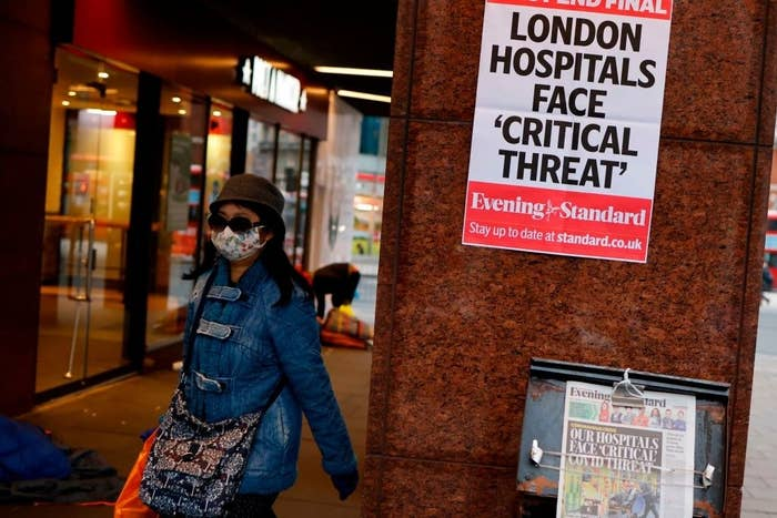 """A woman walks by a sign that says """"London hospitals face 'critical threat'"""""""