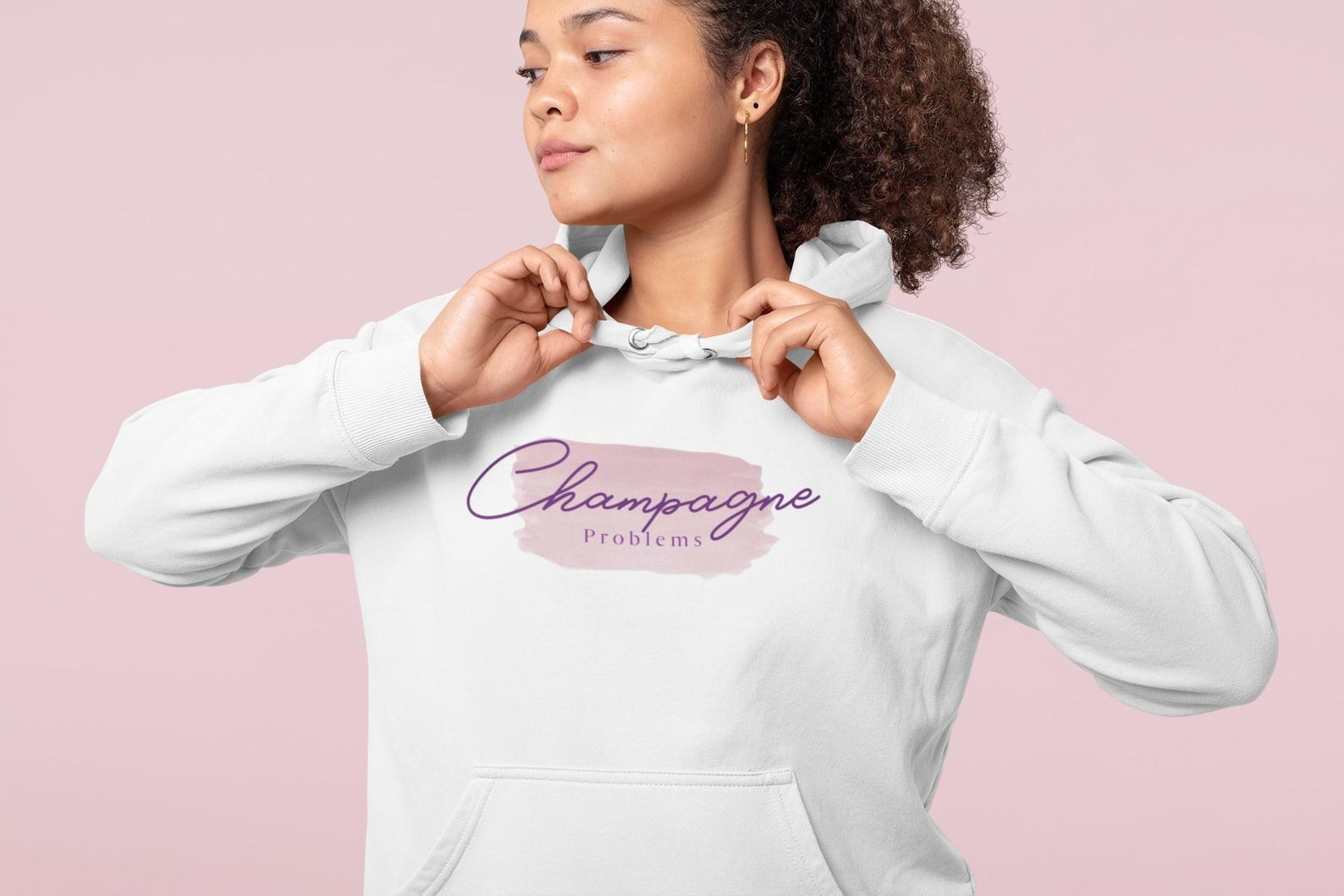 "a model in a white sweatshirt that says ""champagne problems"" on it in purple"