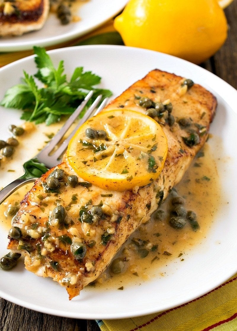 A plate of halibut with lemon caper garlic sauce.