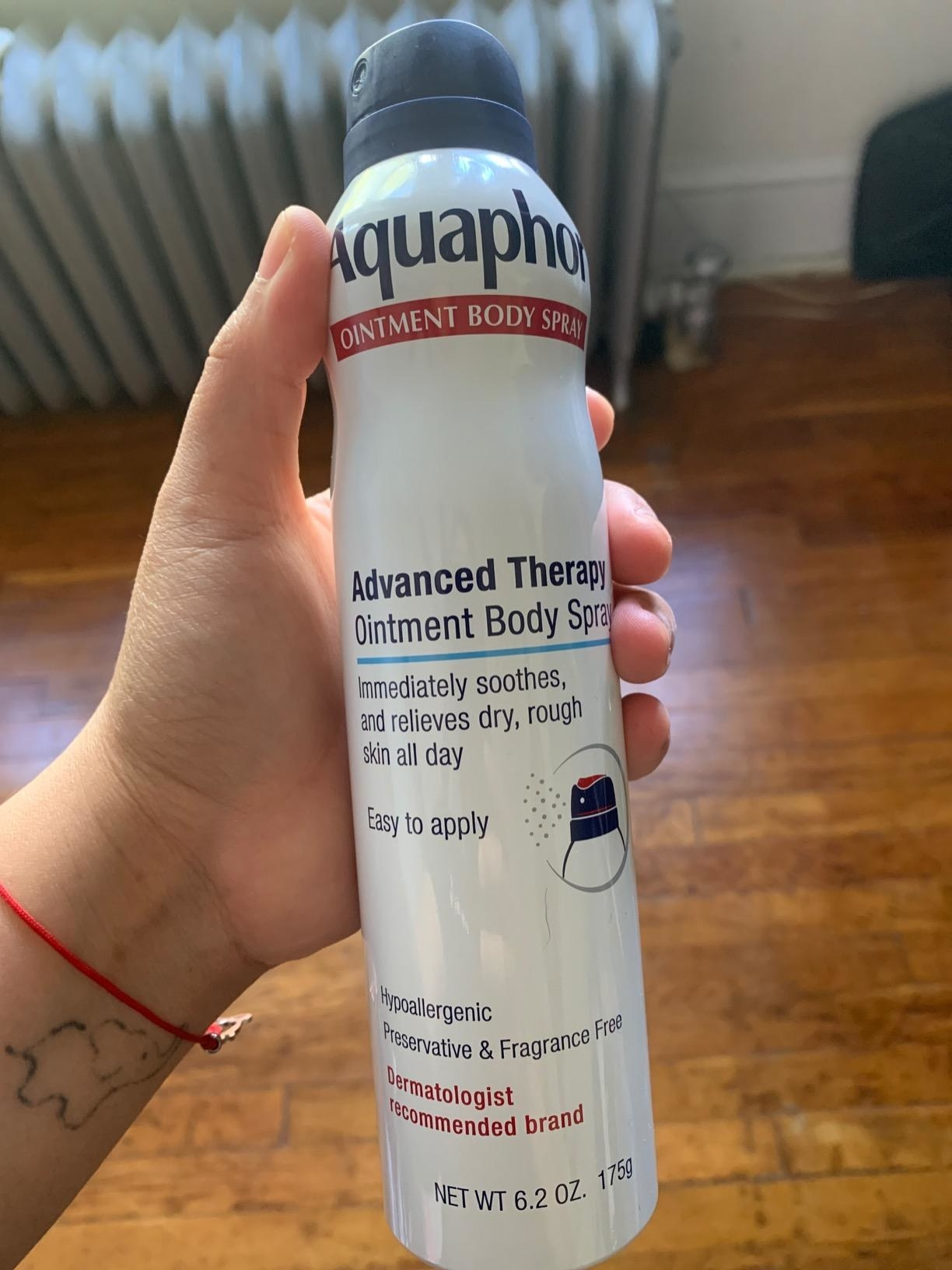 Reviewer holding can of body spray