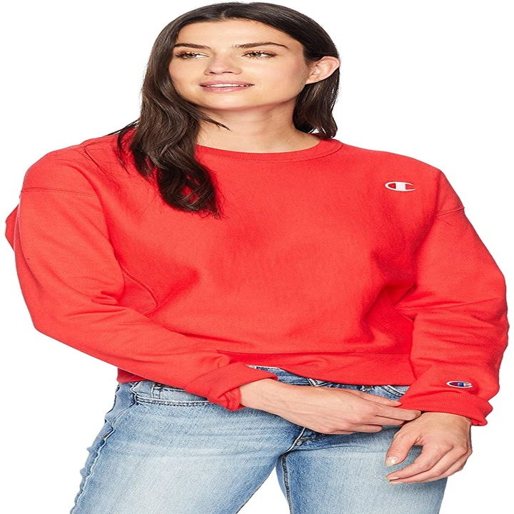 Front view of a model wearing the sweater in spark red