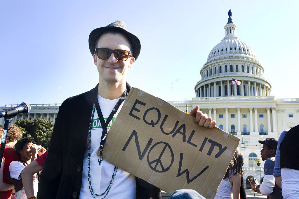 "A man standing outside the Capitol, smiling at the camera and holding a sign that says, ""Equality now"""