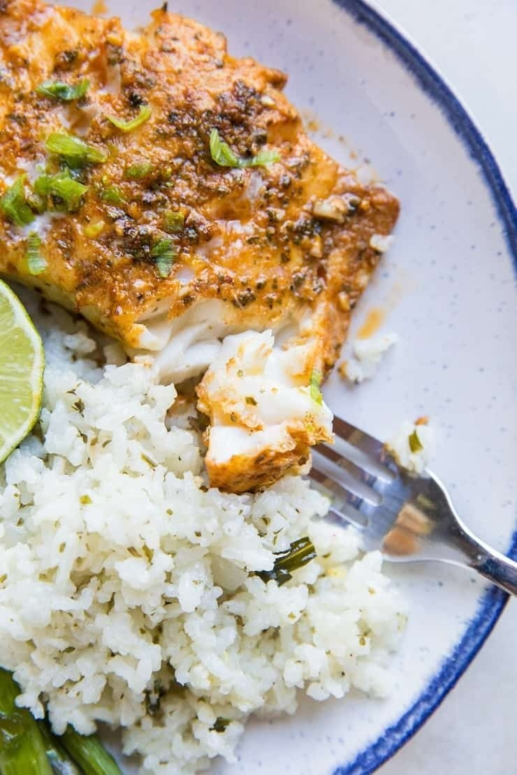 A plate of white rice topped with chili lime cod.
