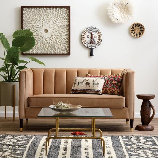 The camel-colored mid-century modern loveseat which has four wooden legs