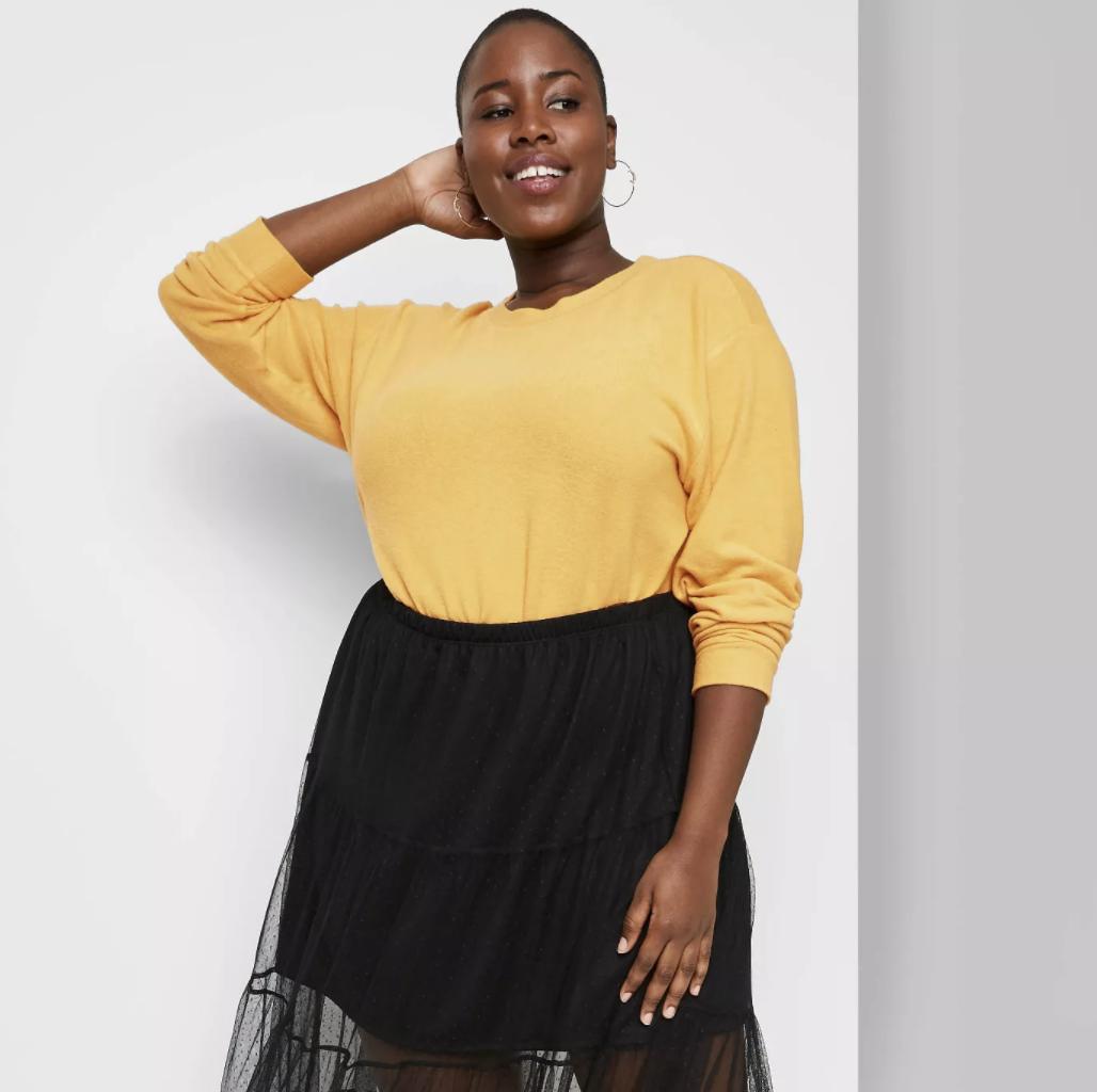 Model wears yellow flowy top