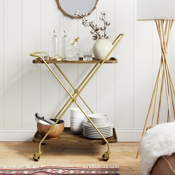 The brass and wood bar cart which has an X design, two shelves, and four wheels