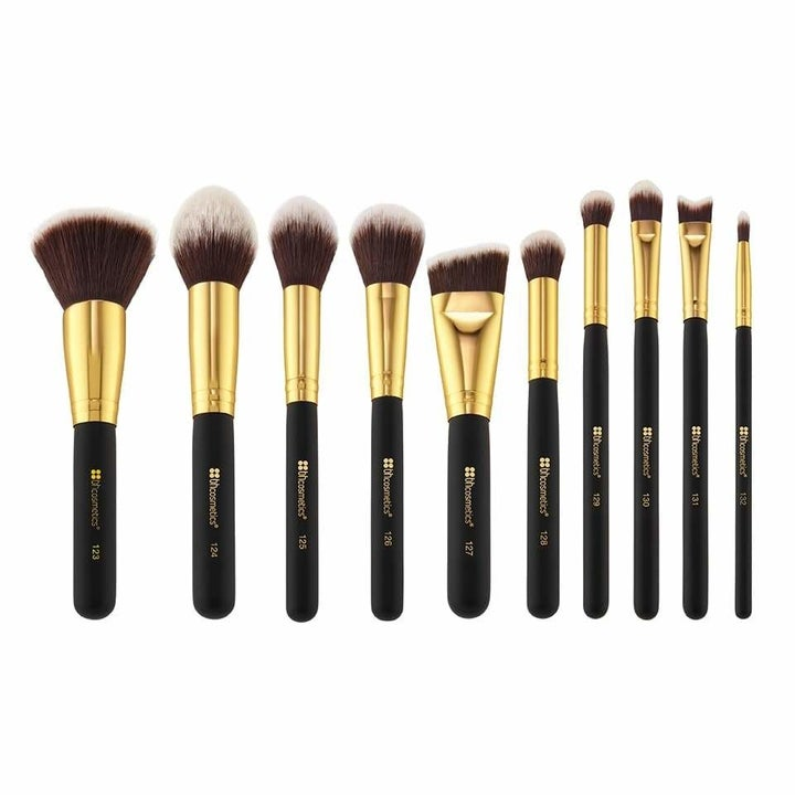a set of makeup brushes with gold accents and black handles