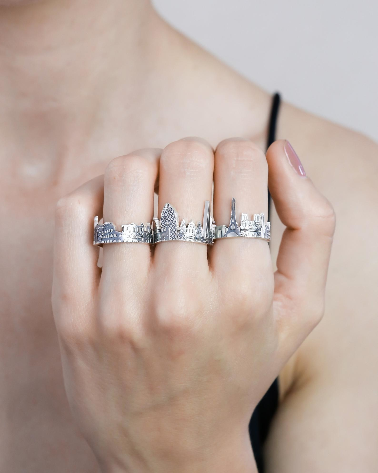 model wearing three rings which are shaped like the skylines of different cities. The one on the pointer finger has a Paris skyline.