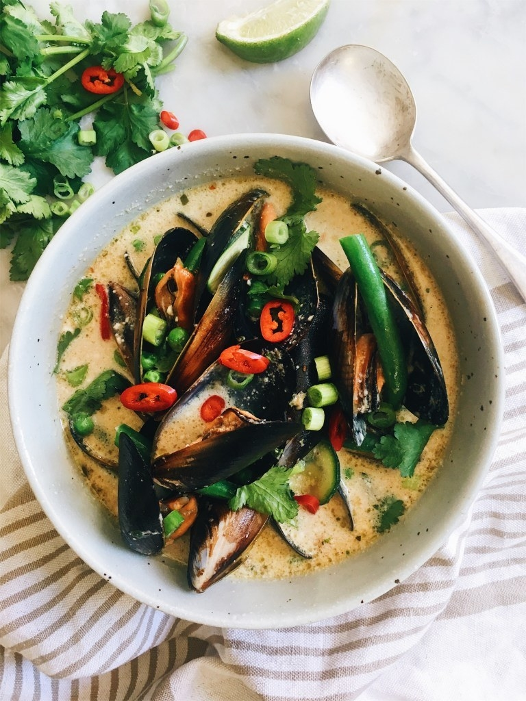 A bowl of mussels in coconut broth with chili and scallions.