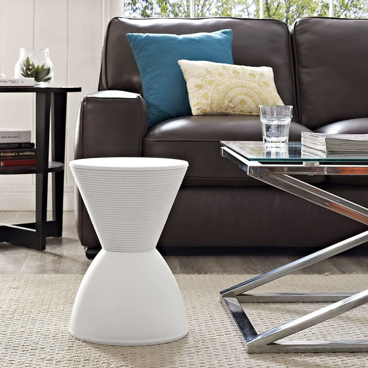The white accent stool which is hourglass shaped