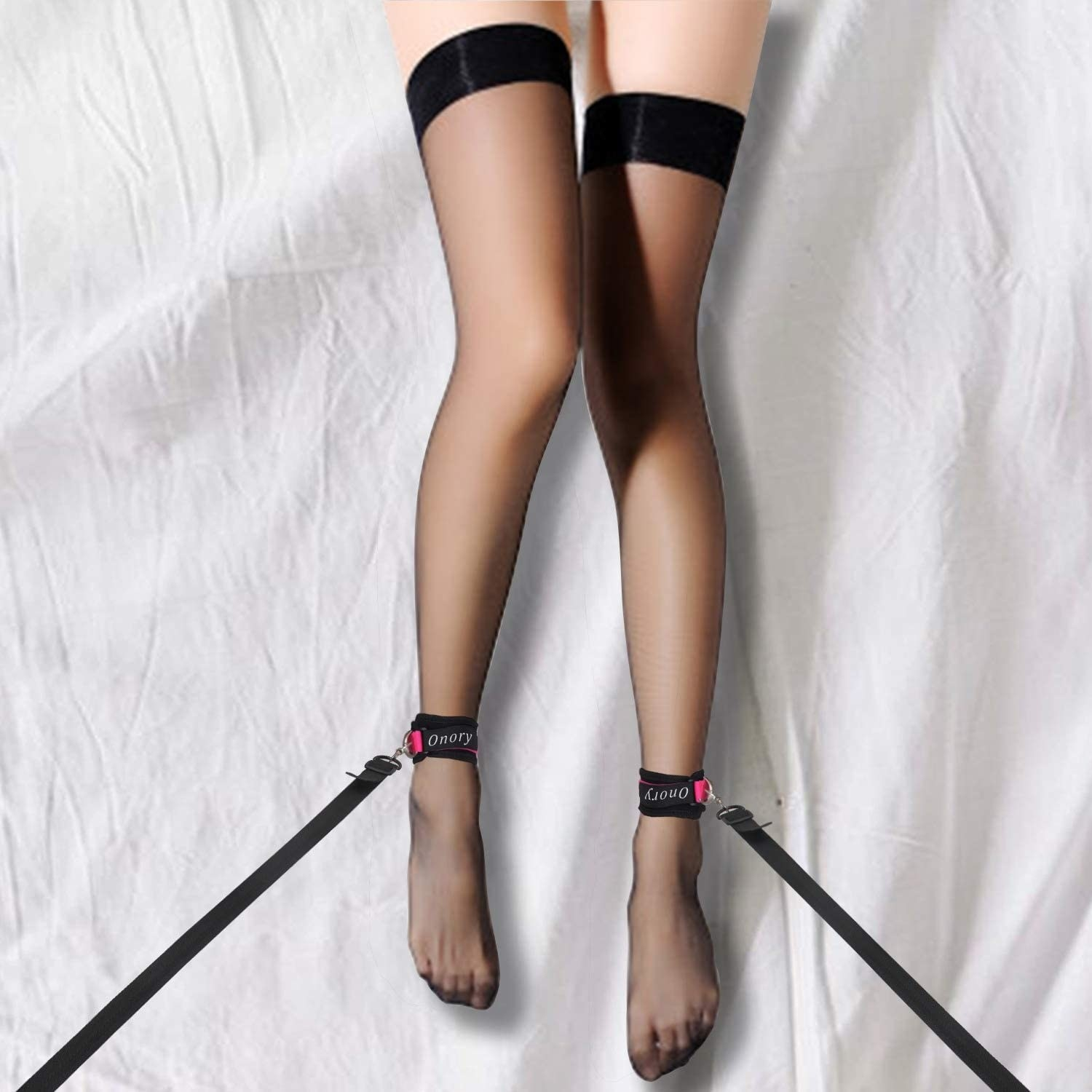 Black and pink ankle restraints on ankles