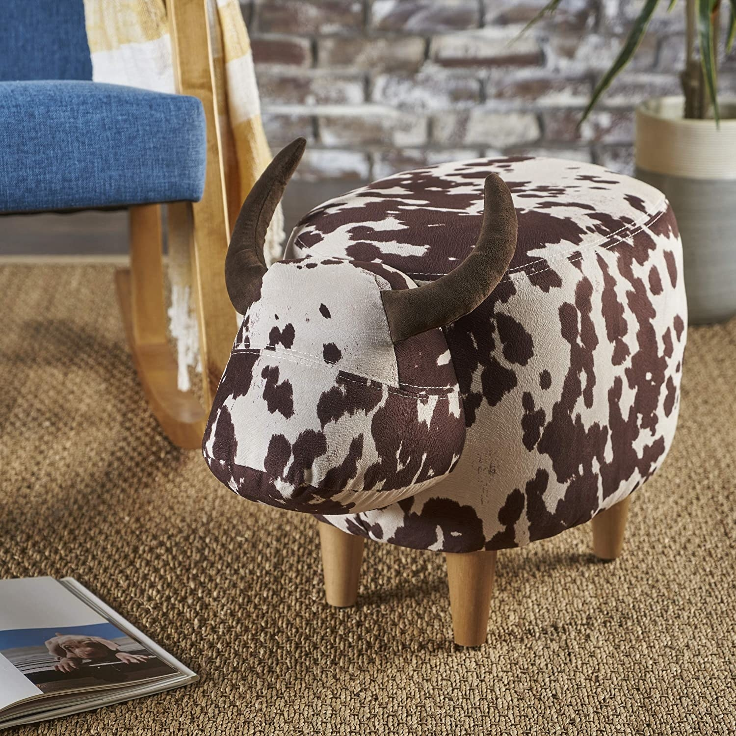 The ottoman which has brown and white cow print, two horns, and four legs