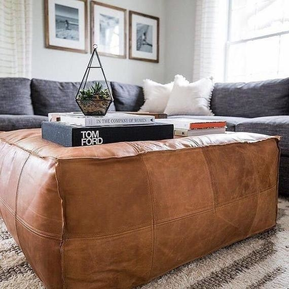 The square leather pouf used as a coffee table