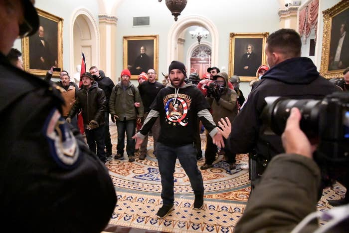 "A man wearing a black T-shirt with ""Q"" and an eagle on it stands in front of a group of maskless men, facing police"