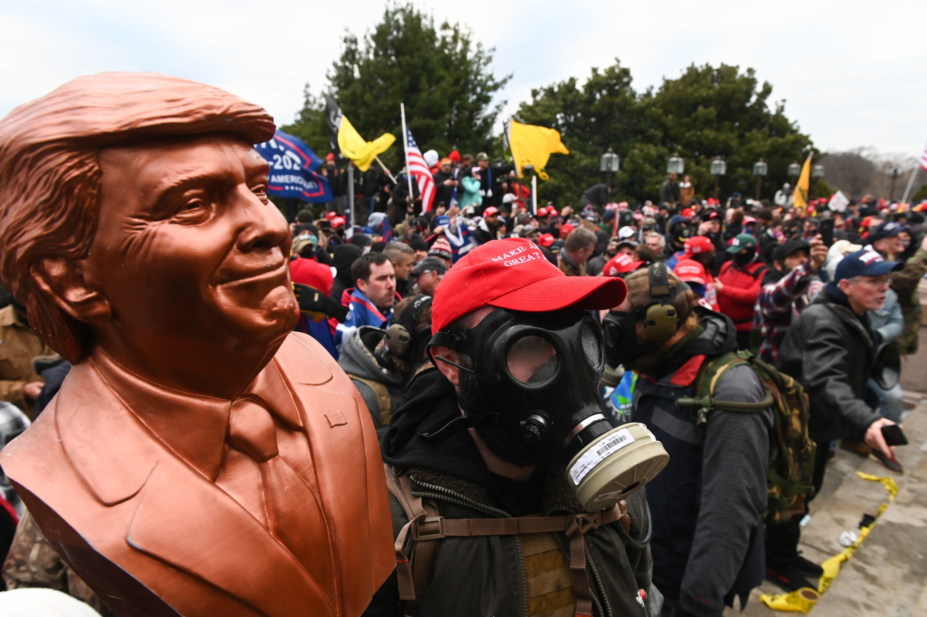 A supporter of President Trump wears a gas mask and holds a bust of him after he and hundreds of others stormed the Capitol