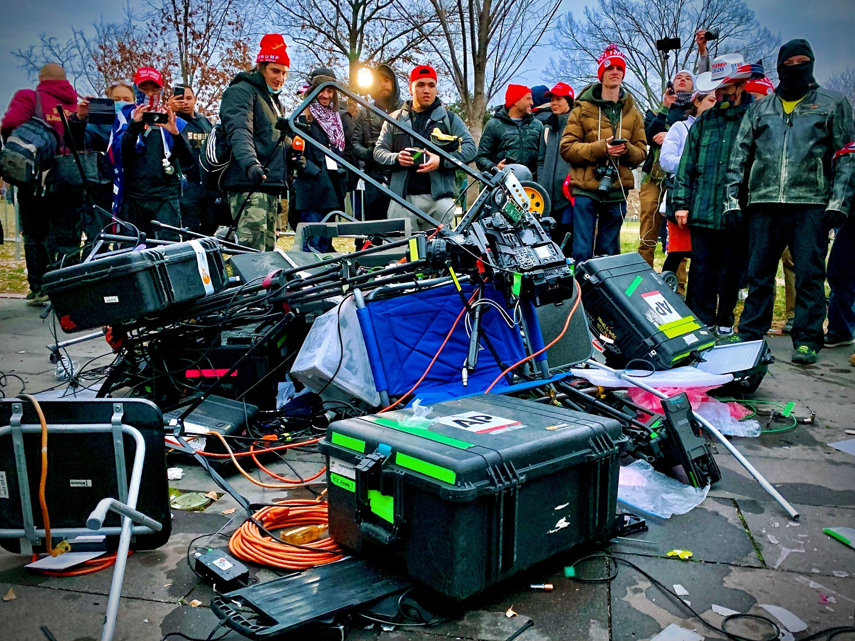 Supporters of US President Donald Trump stand next to media equipment they destroyed during their riot