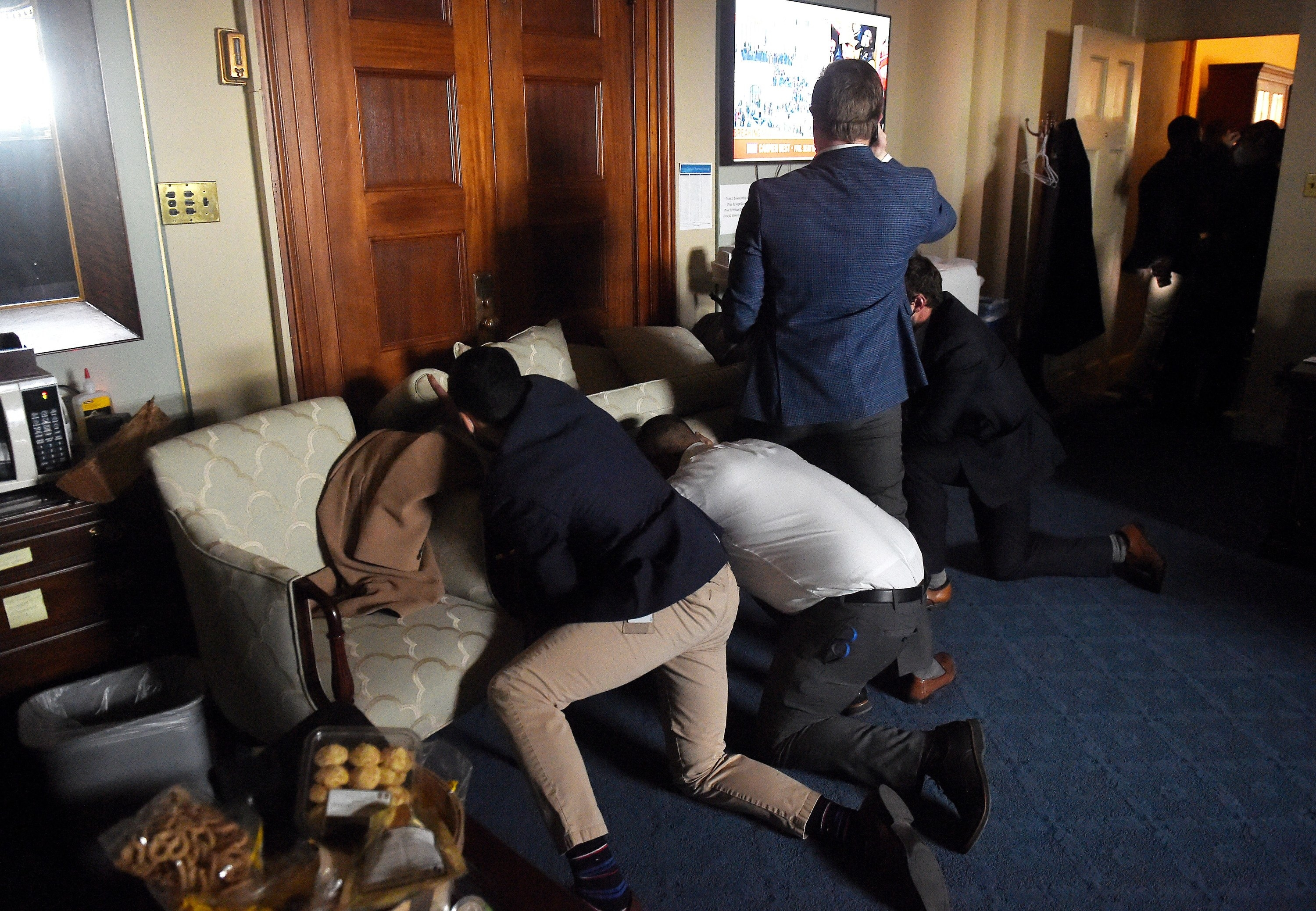 Several people crouched on the floor as they hide behind a barricaded door